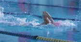 achieve : Side view of a young Caucasian female swimmer training in a swimming pool, crawl