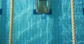 badehose : Overhead view of a young Caucasian male swimmer training in a swimming pool, diving and emerging from water