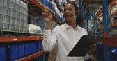 путь : Front view close up of a young mixed race female warehouse manager holding a clipboard and talking on a phone headset in a storage warehouse, with a male member of staff working in the background