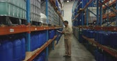 distribuzione : Side view of a middle aged mixed race male warehouse worker making an inspection and writing on a clipboard in a storage warehouse