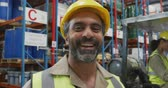 dva lidé : Portrait close up of a middle aged mixed race male warehouse worker wearing a yellow hard hat smiling to camera in a warehouse loading bay, with a colleague in a forklift truck in the background