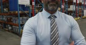 distribuzione : Portrait close up of a middle aged mixed race male warehouse manager smiling to camera with arms crossed in a warehouse loading bay