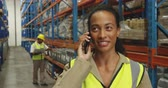 distribuzione : Front view close up of a young mixed race female warehouse worker holding her hard hat and talking on a smartphone and smiling to camera in a storage warehouse, with a male worker busy working in the background