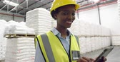 aanraken : Portrait close up of a young mixed race female warehouse manager wearing a yellow hard hat using a tablet computer in a warehouse and smiling to camera