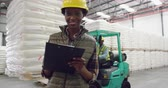 sack : Portrait close up a young mixed race female warehouse manager writing on a clipboard smiling to camera in a warehouse loading bay, with a colleague on a forklift truck in the background