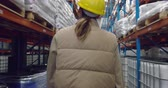 distribuzione : Rear view close up of a young Caucasian female warehouse  manager walking through a storage warehouse