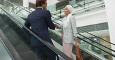 generation z : Side view close up of a young mixed race businesswoman wearing a hijab talking and shaking hands with a young Caucasian businessman while going up on an escalator in a modern office building Stock Footage