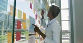 yoğunlaşmak : Side view close up of a young African American businesswoman, a young mixed race businesswoman standing at a glass wall writing on coloured sticky notes in a modern office Stok Video