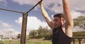 obstacle course : Front view close up of a young Caucasian man hanging from a climbing frame at an outdoor gym during a bootcamp training session