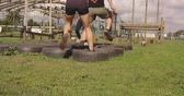 concorrentes : Rear view of a young Caucasian woman and a young Caucasian man stepping through tyres at an outdoor gym during a bootcamp training session, with another participant in the background