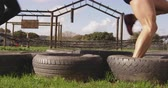 obstacle course : Side view low section of two young Caucasian women stepping through tyres at an outdoor gym during a bootcamp training session Stock Footage