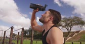 cansado : Side view close up of a young Caucasian man pouring water from a water bottle over his head to cool down at an outdoor gym during a bootcamp training session