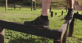 engel : Side view low section of a young Caucasian man walking along a beam at an outdoor gym during a bootcamp training session