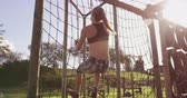 obstacle course : Rear view of a young Caucasian woman climbing on nets on a climbing frame at an outdoor gym during a bootcamp training session