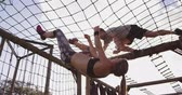 engel : Side view of a young Caucasian woman and a young Caucasian man climbing on nets on a climbing frame at an outdoor gym during a bootcamp training session