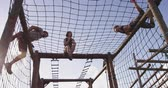 obstacle course : Side view of a young Caucasian woman and a young Caucasian man climbing over nets on a climbing frame at an outdoor gym during a bootcamp training session, while another female participant sits on the frame clapping Stock Footage