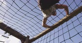 obstacle course : Low angle view of a young Caucasian man climbing over nets on a climbing frame at an outdoor gym during a bootcamp training session Stock Footage