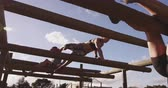 ekipman : Low angle view of two young Caucasian women and a young Caucasian man climbing between poles on a climbing frame at an outdoor gym during a bootcamp training session