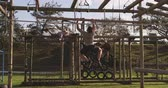 obstacle course : Rear view of a young Caucasian man  hanging from a beam crossing a climbing frame at an outdoor gym during a bootcamp training session, with another participant climbing in the background Stock Footage