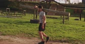 ekipman : Side view of a young Caucasian man carrying a log of wood on his shoulder and running at an outdoor gym during a bootcamp training session
