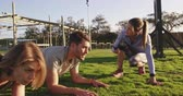 obstacle course : Side view of a young Caucasian woman and a young Caucasian man doing the plank exercise with a young Caucasian female trainer timing them with a stopwatch at an outdoor gym during a bootcamp training session