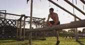 obstacle course : Side view of a shirtless young Caucasian man vaulting over a hurdle at an outdoor gym during a bootcamp training session Stock Footage