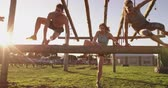 arranque : Front view of two young Caucasian women and a young Caucasian man vaulting over a hurdle at an outdoor gym during a bootcamp training session Stock Footage
