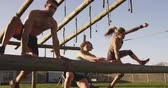 generation z : Side view of two young Caucasian women and a young Caucasian man vaulting over a hurdle at an outdoor gym during a bootcamp training session