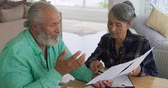 papierwerk : Front view close up of a mature mixed race couple holding documents and talking at home Stockvideo