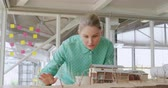 architectural model : Front view of a happy young Caucasian female business creative working in a modern office, checking a 3d architectural model Stock Footage