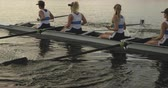 visier : Side view of a team of four young adult Caucasian women rowing in a racing shell on a river