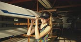 boot : Front view of a young adult Caucasian female rower standing in a boatshed holding one end of a racing shell before training on a river