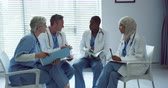фрак : Front view of Multi-ethnic doctors discussing over medical files in hospital. They are sitting together