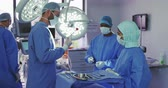 krev : Side view of Caucasian surgeon performing operation in operation theater. They are holding surgical instruments Dostupné videozáznamy