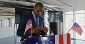 presidential candidate : Side view close up of a serious young African American man standing at a lectern decorated with a US flags addressing the audience at a political rally