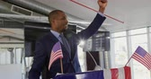 presidential candidate : Side view close up of a smiling young African American man standing on a podium decorated with a US flag shouting and raising his fist in triumph at a political rally