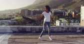 чувственный : Side view of a hip young mixed race woman walking, turning round on an urban rooftop with buildings in the background, swinging her jacket Стоковые видеозаписи