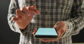trabalhar fora : Front view mid section of a young Caucasian woman wearing a checked shirt using a smartphone, scrolling and zooming on the touchscreen