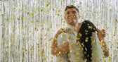 noeud papillon : Close up of a happy young Caucasian bride and groom in traditional formal clothes dancing together closely under falling golden confetti and embracing in front of a curtain of shiny silver fringes, backlit by a spotlight Vidéos Libres De Droits