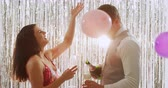 champanhe : Side view close up of a smartly dressed young Caucasian couple pouring glasses of champagne, drinking a toast and laughing at a party, with balloons falling, in front of a curtain of shiny silver fringes, backlit by a spotlight