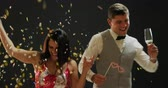 торжества : Front view close up of a smartly dressed smiling young Caucasian couple holding glasses of champagne, dancing under falling confetti and balloons, and posing for a picture with party photo props at a party, against a black background