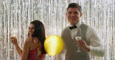 festividades : Front view close up of a smartly dressed young Caucasian couple drinking glasses of champagne, smiling and dancing at a party, with balloons falling, in front of a curtain of shiny silver fringes, backlit by a spotlight