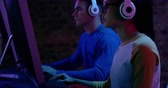 электроника : Side view close up of a young mixed race woman and a Caucasian man sitting beside each other working at computers wearing headphones in a darkly lit workspace Стоковые видеозаписи