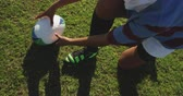 ラグビー : High angle low section of a young adult mixed race female rugby player sitting on a rugby pitch and tying her boot with the ball beside her, picking up the ball and walking with it to her teammates, t