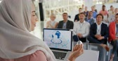 аплодисменты : Over the shoulder close up view of a young Asian businesswoman wearing a hijab standing on a stage at a lectern with a laptop speaking and gesturing to the audience at a business conference. The seated audience are seen facing her in the background and ap