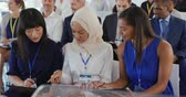 yarış : Front view close up of two young Asian businesswomen, one wearing a hijab, and a mixed race young businesswoman sitting in a row in the audience at a business seminar talking and looking at the notes they have been making, other members of the diverse aud