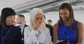 説明する : Front view close up of two young Asian businesswomen, one wearing a hijab, and a mixed race young businesswoman sitting in a row in the audience at a business seminar talking and looking at the notes  動画素材