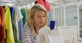 concentrando : Front view of young Caucasian woman sitting at a sewing machine working in a modern fashion studio, with a mannequin and clothes on a rail in the background Stock Footage