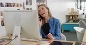 jedna osoba : Front view of a young Caucasian female business creative using a computer and talking on the phone in a modern office