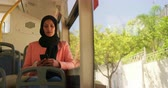 pendulares : Front view of a young mixed race woman wearing a hijab commuting sitting on a bus in a city, using a smartphone